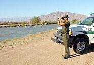 Border Patrol agent watches the line through binoculars