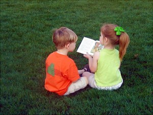 Girl reading story to boy