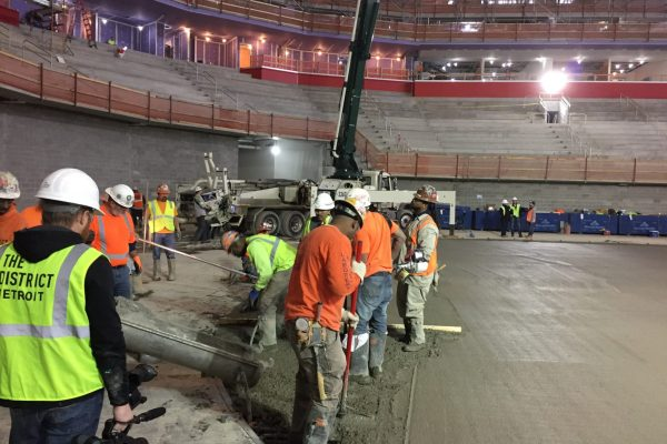 11workers lay down concrete at Little Caesars Arena