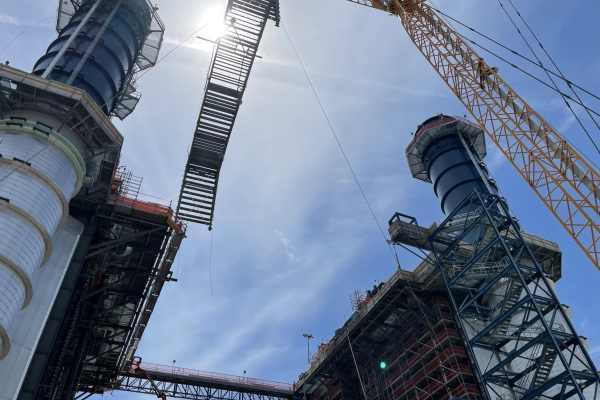 11crane lifting metal crane into air at Kiewit Power construction site