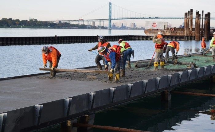 Workers laying concrete on dock
