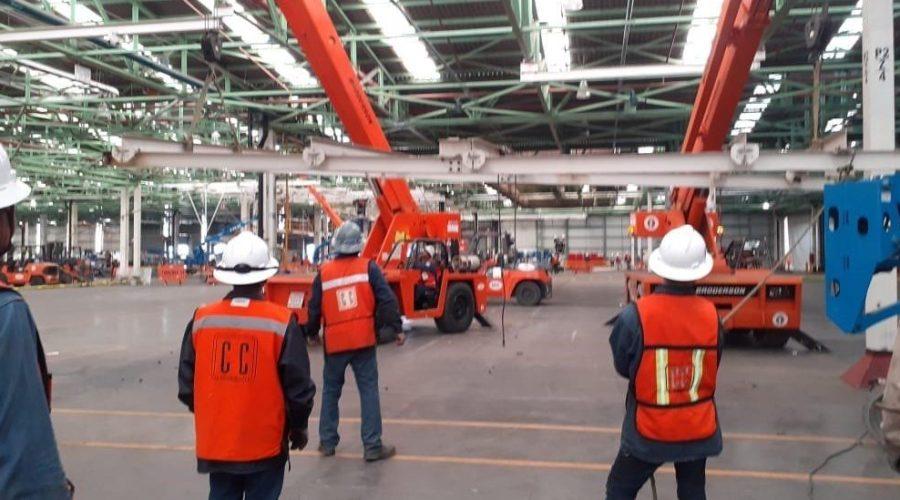 workers on plant floor with orange skyjacks