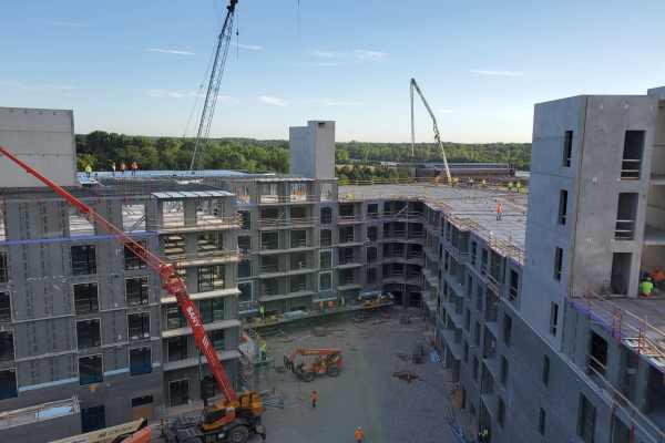 11gray building mid-construction with orange crane