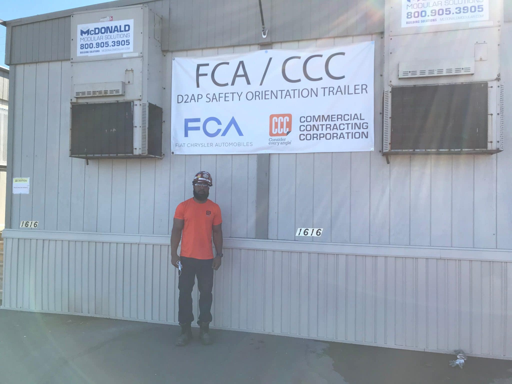 man in protective glasses stands below FCA/CCC sign