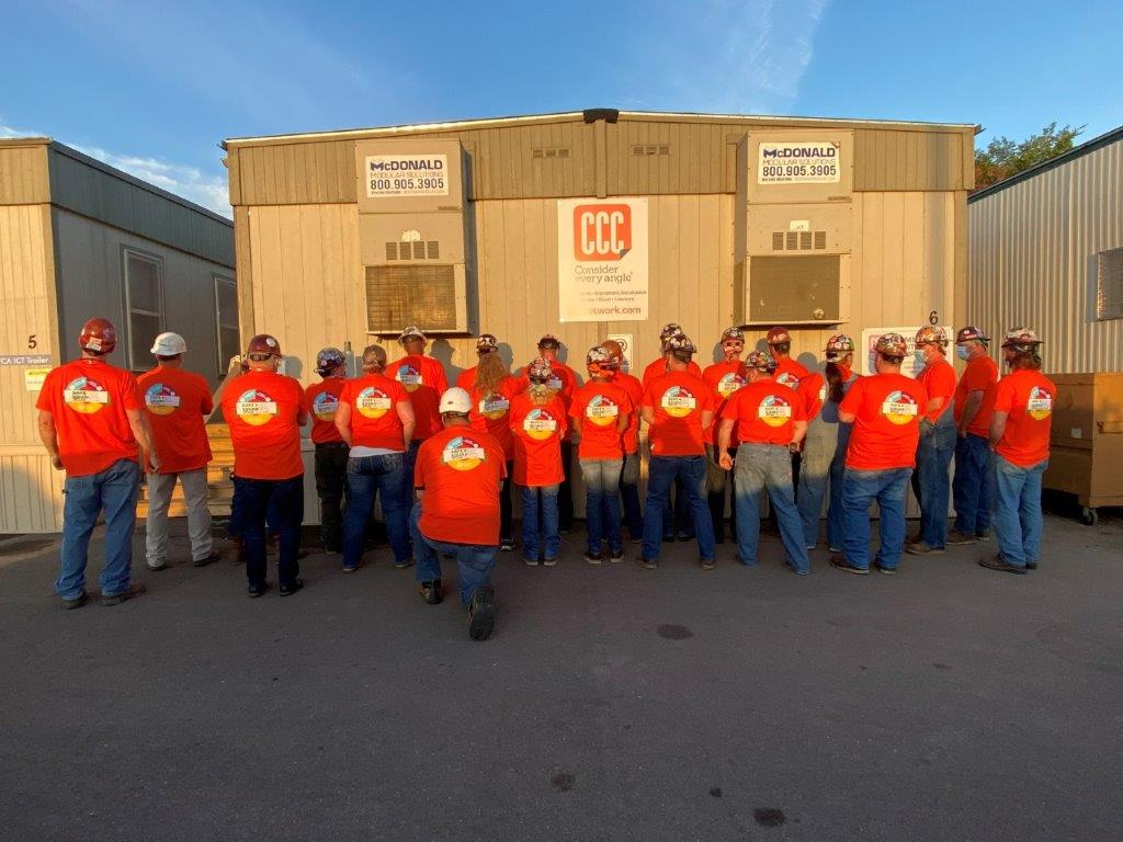 construction workers in orange shirts face away from camera