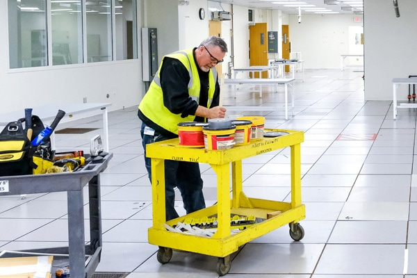 Man leans over yellow work cart