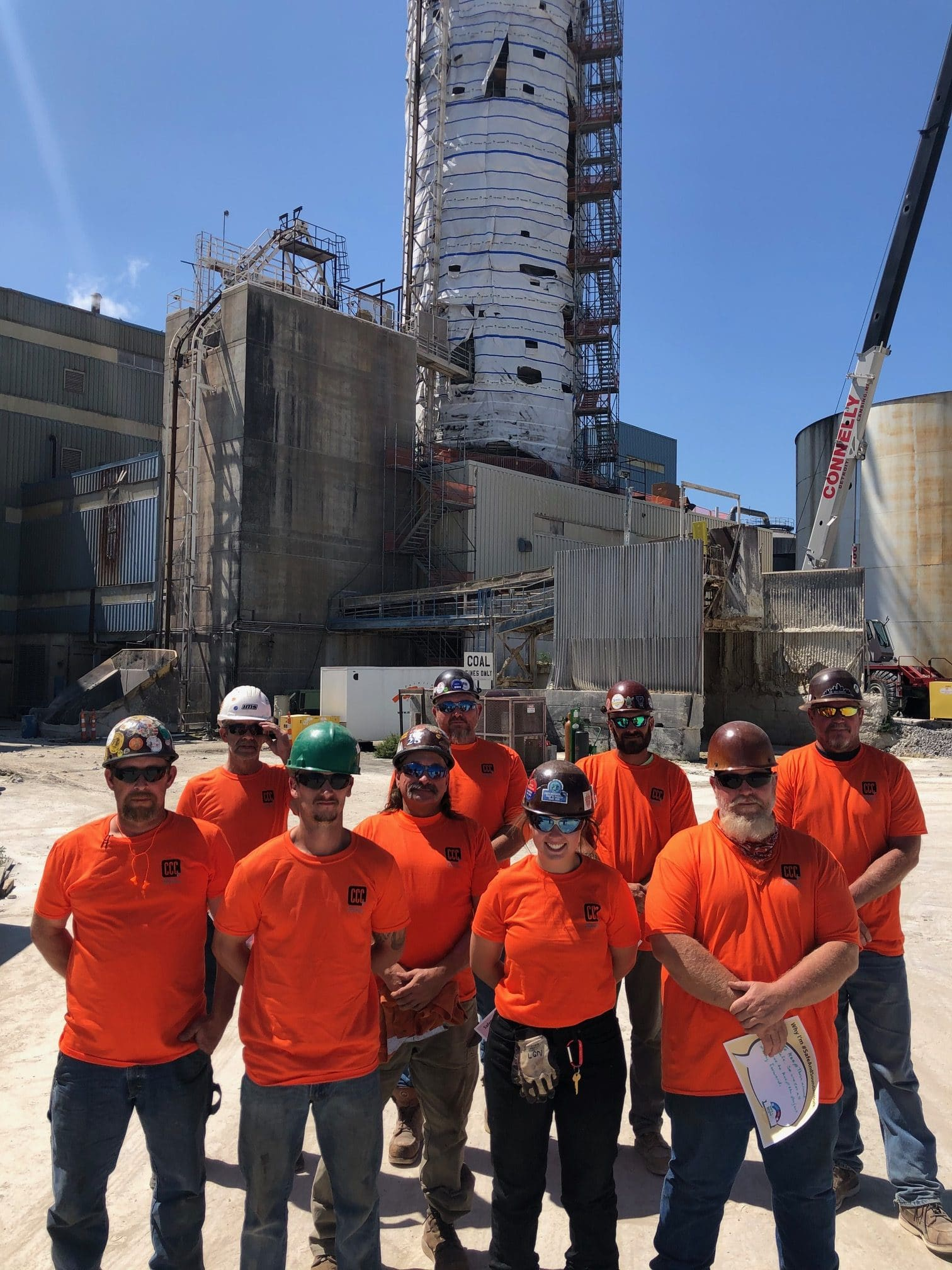 construction worker group photo in orange shirts (verticle)