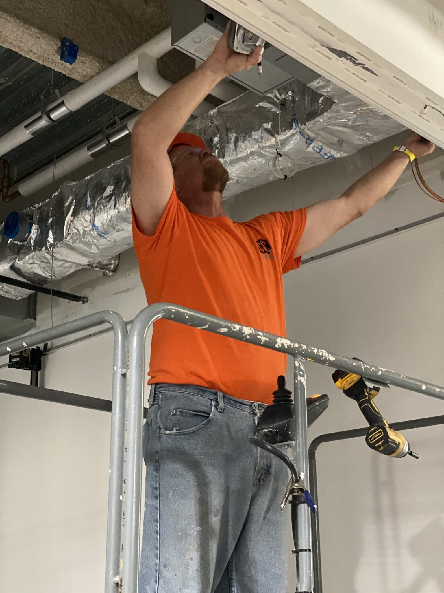 construction worker in orange shirt installs wiring