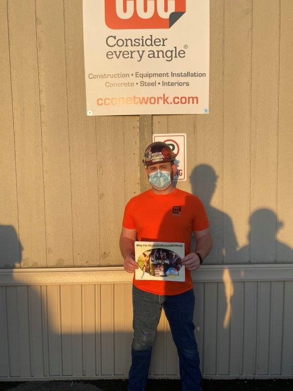 construction worker in mask holds sign with pictures of family