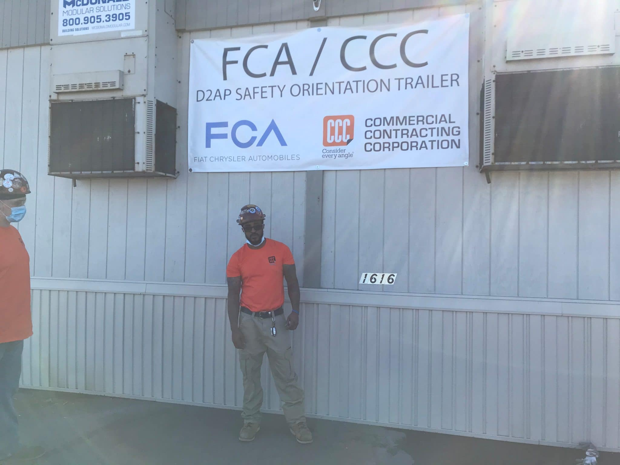 man in orange shirt poses under FCA, CCC sign