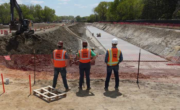 three construction workers look down at concrete site (square)