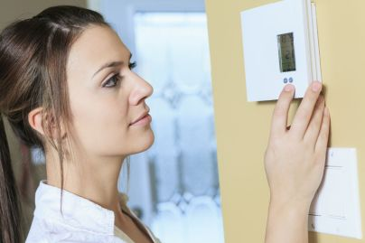 Woman adjusting her thermostat after a heating installation in mount pleasant