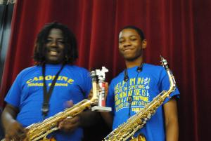 two students with saxophones and trophies