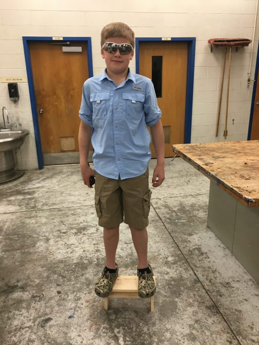 agriculture student standing on footstool he made