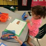 Student coloring a brown bear