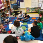 Students partnered up and reading on the carpet