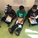 Three students reading on the floor