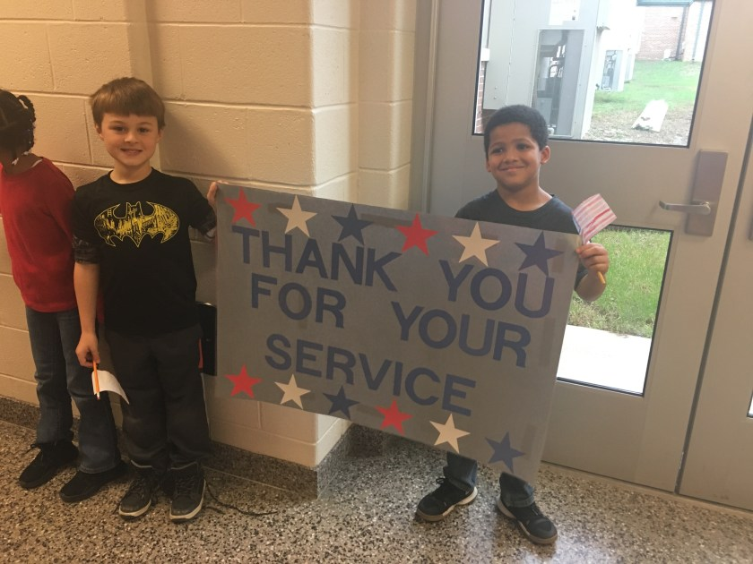 "Students holding sign that says ""Thank you for your service"""