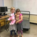 Two girls smiling with their stuffed animals