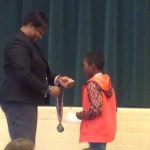 Mrs. Haley presenting a medal to a student