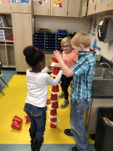 Three students stacking cups
