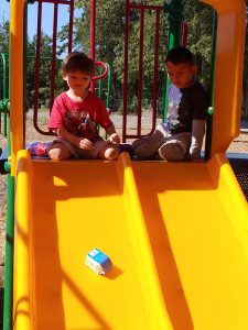 Two students watching a milk carton go down a slide