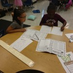 Two 3rd graders playing a place value game