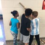 Three students tape roller coaster tracks to wall
