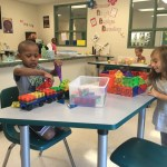 Students building with magnetic blocks