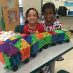 Students smile while showing their train