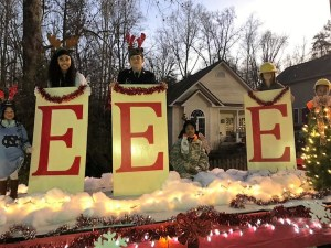 3 students standing on float with E signs