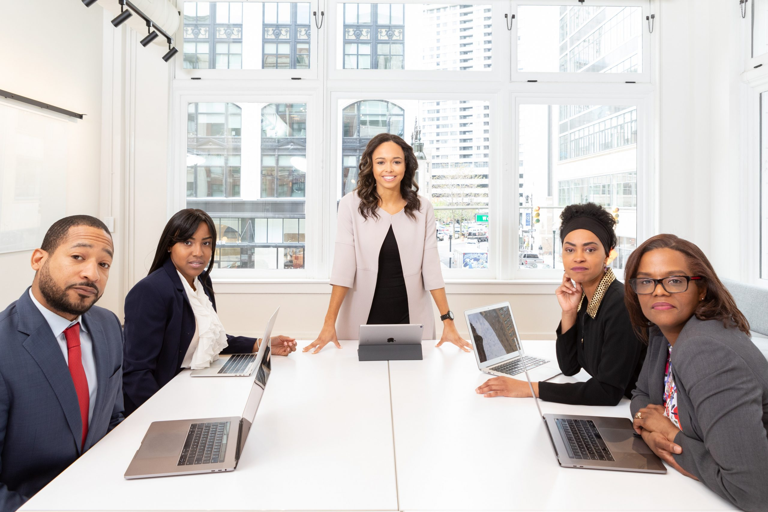 woman-standing-on-the-center-table-with-four-people-on-the-Pexel