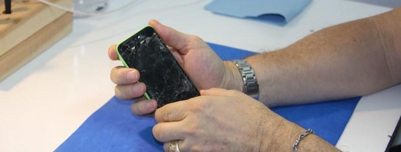 holding broken smartphone screen