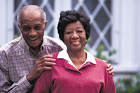 An older man and woman standing in front of a house.  Both are smiling into the camera.  The man is standing behind the woman with his hands on her shoulders.
