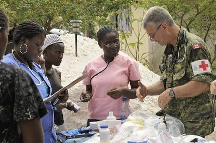 Captain Real Herbert and two Haitian doctors discuss medication dosages during a joint Mobile Medical Clinic at Leogane, Haiti.