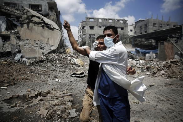 A medic helps a Palestinian in the Shejaia neighbourhood, which was heavily shelled by Israel during fighting, in Gaza City July 20, 2014.