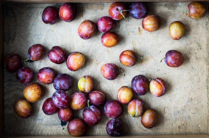 owoce śliwy w pudle drewnianym