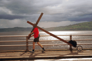Man carrying wooden cross along footpath