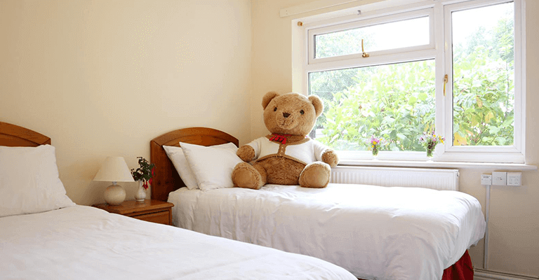 large teddy bear sat on twin bedroom, next to large window