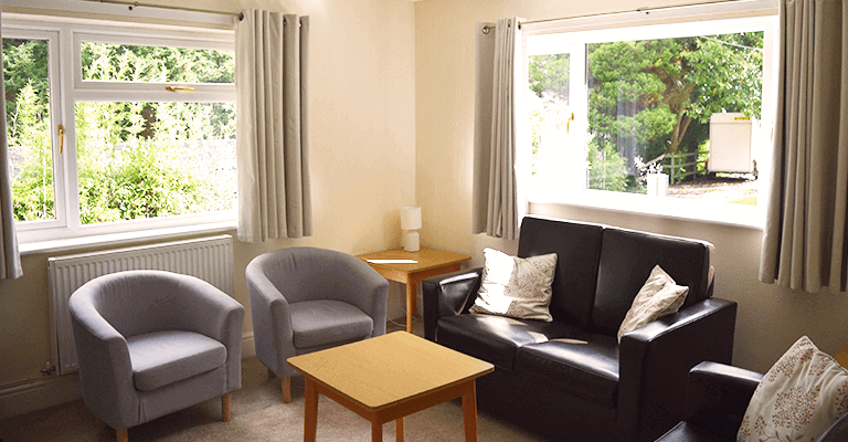 Living room with individual chairs and sofa located next to two large windows
