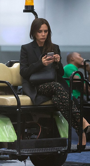 Victoria Beckham, her own coat, bag and Victoria Beckham Floral stretch-jacquard skinny pants with Casadei shoes, checks her phone while being driven through the terminal at Miami International Airport on June 7, 2015.