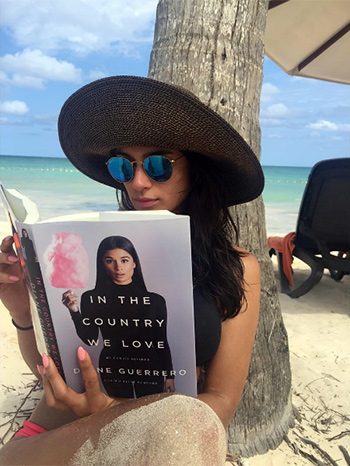 "Orange is The New Black star Diane Guerrero wearing a pair of Ray-Ban Polarized Round Metal-Frame Sunglasses with Blue Mirror Lens and holding her new book ""In the Country We Love""."