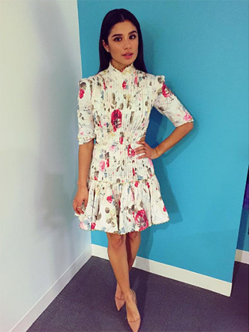"Orange is The New Black star Diane Guerrero wears a Zimmermann Mischief Floral-Print Pleated Linen Dress while promoting her new book ""In the Country We Love""."