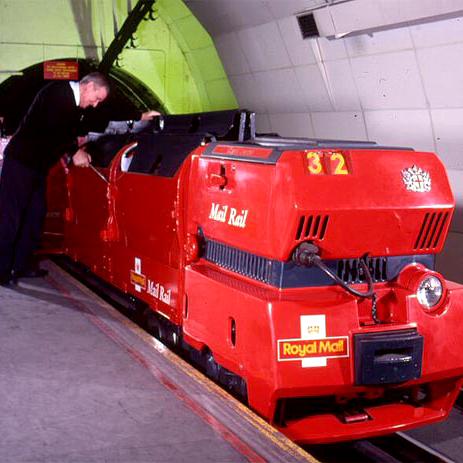 Man working on red Royal Mail postal train