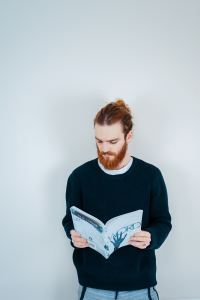 Man with red hari and beard reading magazines against a white background