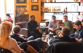 students discussing a project at The Hub Coffeehouse
