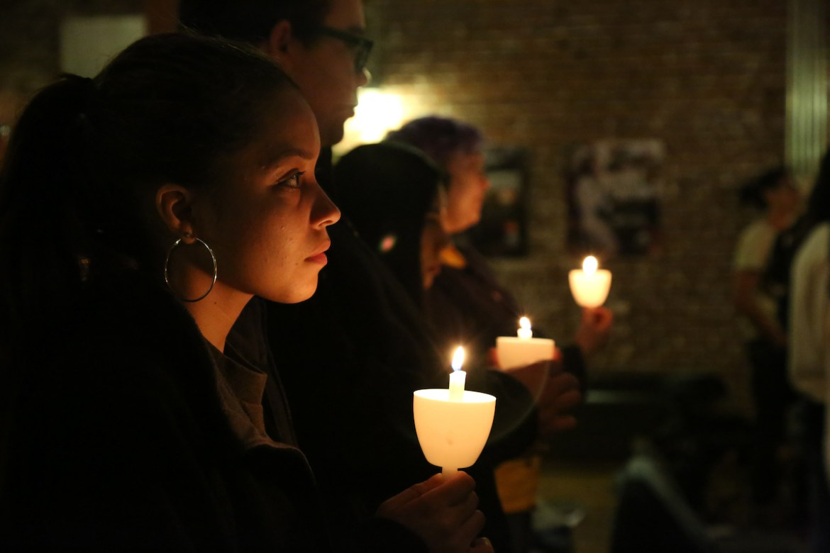 students holding candles at a refugee vigil