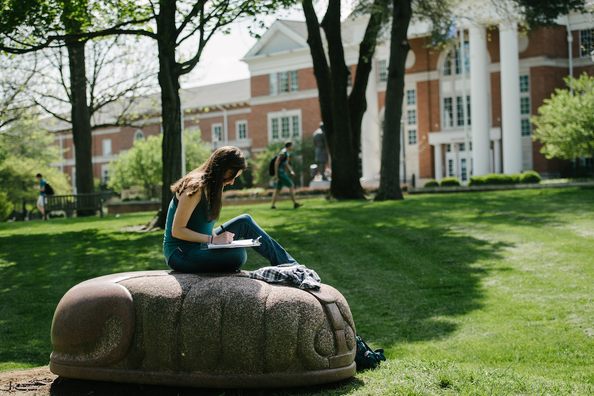 female student studying atop the Palace of Memory sculpture
