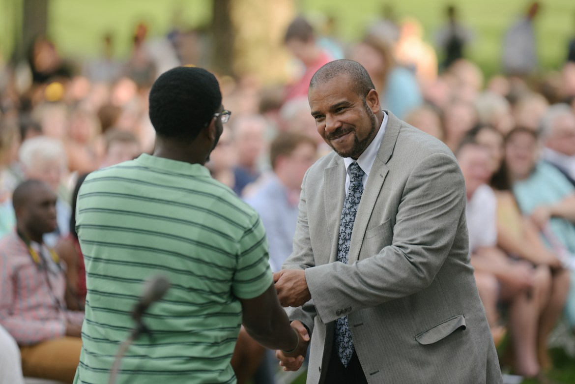 Dr. Rodman King shakes hands with a male student at Honor Walk