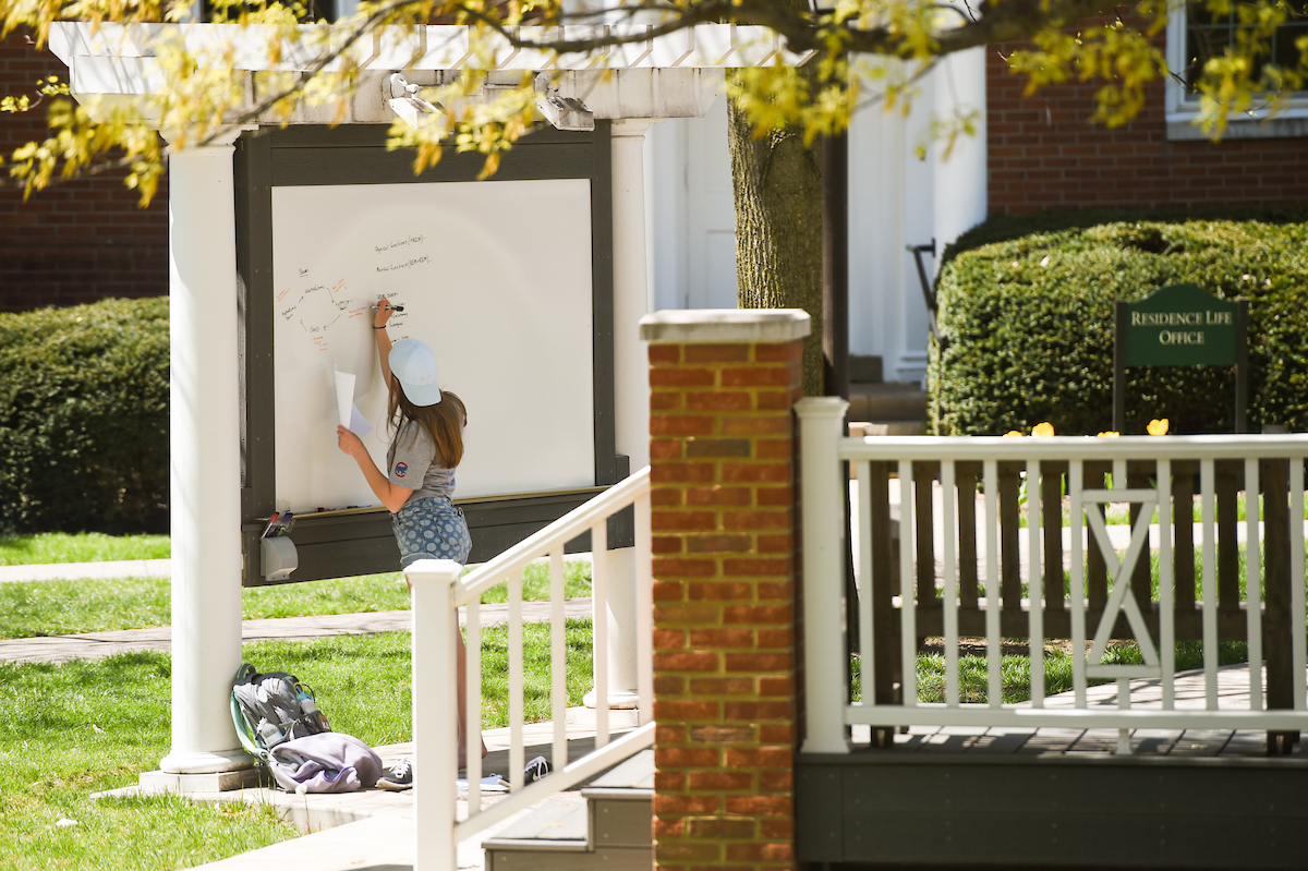 a student using the white board in the Buchanan Outdoor Classroom